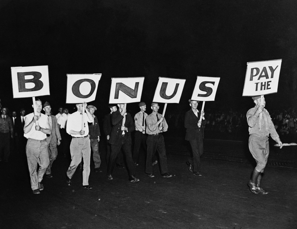 """. The \""""Pay the Bonus\"""" sign carried by this group of World War I veterans was typical of the banners throughout the demonstration in Washington, June 7, 1932.  Marchers are shown walking down Pennsylvania Avenue toward the Capitol. (AP Photo)"""