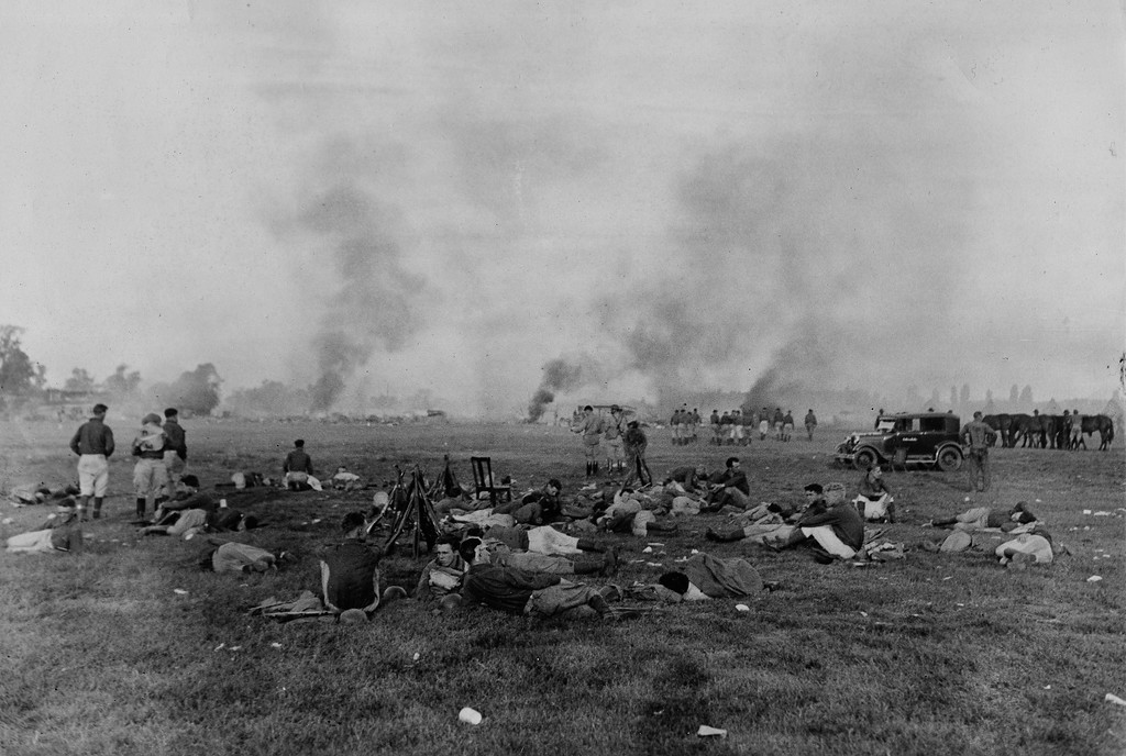 . The smoldering ruins of a Bonus Army camp is shown the morning after they were set on fire during evacuations proceedings when government troops were called out, in Washington, D.C., July 29, 1932. Many of the troops are shown resting in front. (AP Photo)
