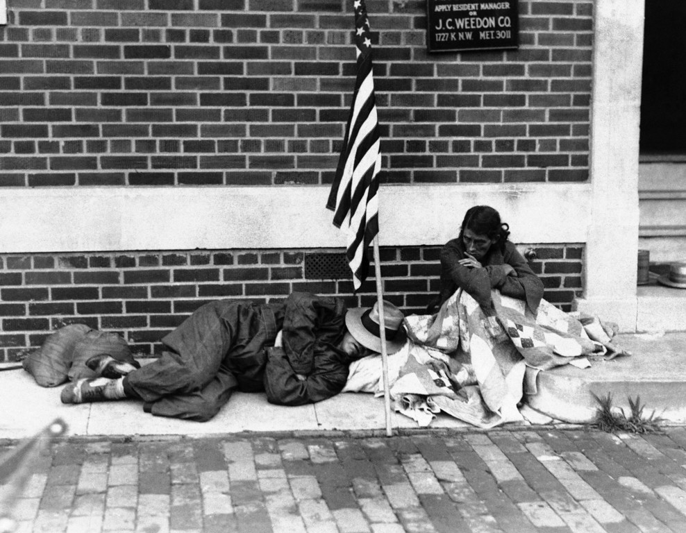 . A war veteran and his wife huddle in the street the morning after the eviction of bonus-demanding veterans and the burning of their camp by government troops in Washington, D.C., July 28, 1932. He is sleeping on the sidewalk while his wife sits by wrapped in the blankets that comprised their sole belongings. (AP Photo)
