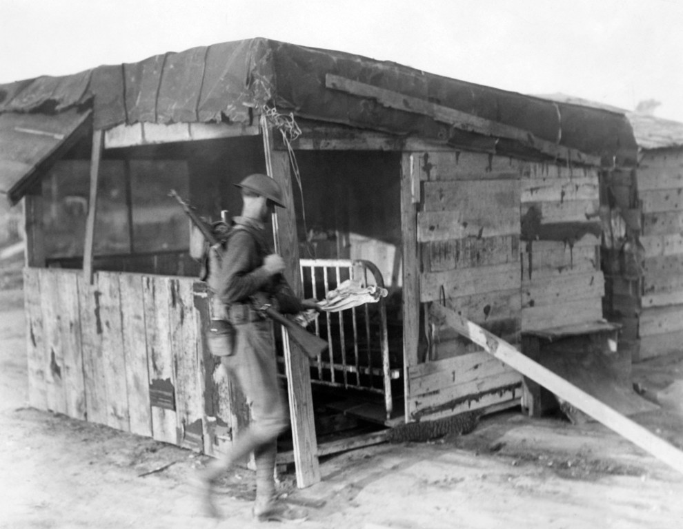 . A regular army enlisted man sets fire to one of the few ramshackle huts at Camp Marks, Anacostia, that were spared by the flames that consumed most of the Bonus Expeditionary Forces encampment, yesterday. Details broke down the camp structures that remained, July 29, 1932. (AP Photo)