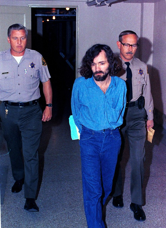 . FILE **This Aug. 20, 1970 file photo shows Charles Manson, head of the cult the Manson Family being escorted by deputy sheriffs on his way to court, in Los Angeles, Calif., after being charged with murder-conspiracy in the Tate-LaBianca slayings.  (AP Photo/FILE)