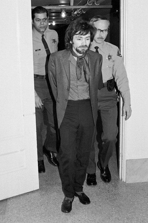 . Charles Manson wears a completely new outfit of jacket, shirt, kerchief, slacks and shoes as he arrives in the Los Angeles Hall of Justice to listen to defense arguments in his trial for murder in the deaths of Sharon Tate and six others, Dec. 29, 1970.  Because of past outbursts, Manson and three women defendants are listening to proceedings via an amplification system in a room adjoining the courtroom. (AP Photo/Wally Fong)
