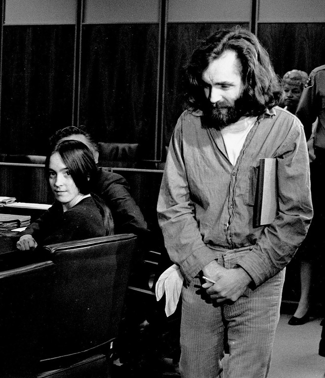 ". FILE - In this Oct. 13,1970 file photo, cult leader Charles Manson walks into the courtroom as Susan Atkins, a member of his family of followers, looks on in Santa Monica, Calif.  A marriage license has been issued for Manson to wed 26-year-old Afton Elaine Burton, who left her Midwestern home nine years ago and moved to Corcoran, California to be near him. Burton, who goes by the name ""Star,\"" told the AP that she and Manson will be married next month. (AP Photo/File)"