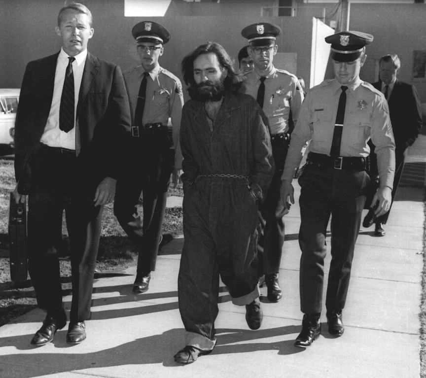 . Charles Manson is escorted by officers while enroute to court in Independence, Calif., in this Dec. 3, 1970 photo.  Manson and three women codefendents were convicted and sentenced to death after the 10-month trial that involved the murders of actress Sharon Tate and six others in the hills near Hollywood, Calif.  Their sentences were later commuted to life when the death penalty was briefly outlawed.  (AP Photo)