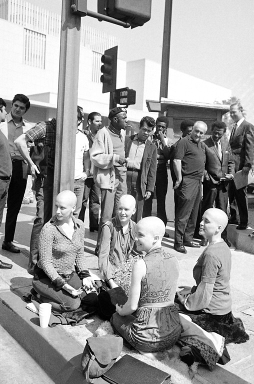 ". Four young members of the Charles Manson ""family,"" with their heads shaved, kneel on the sidewalk outside the Los Angeles Hall of Justice, March 29, 1971. They\'ve kept a vigil at the building throughout the long trial in which Manson and three other women were convicted of slaying actress Sharon Tate and six others. Left to right: Cathy Gillies, Kitty Lutesinger, Sandy Good, Nancy ""Brenda"" Pitman. Jurors were believed near a verdict on the penalty to be imposed on the defendants. (AP Photo/George Brich)"