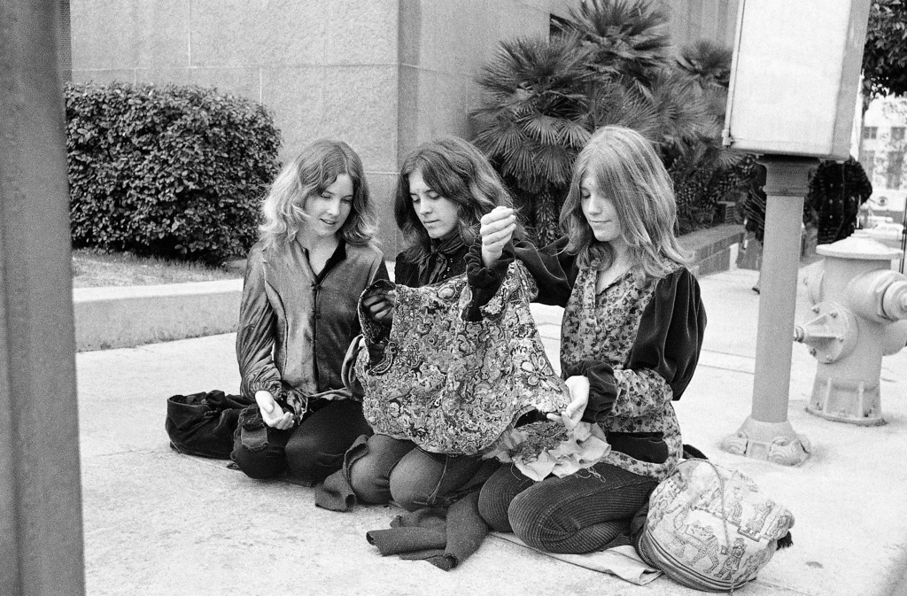 ". Three members of Charles Manson ""family"" work on a multi-colored vest intended for the leader of the hippie-style clan, who is on trial for murder, along with three other women followers, Jan. 24, 1971. Female members of the group have been camping outside the Los Angeles, Calif., courthouse where the seven-month-long trial is nearing its end. Left to right: Sandra Good, Nancy ""Brenda McCann"" Pitman, and Kitty Lutesinger. (AP Photo/David F. Smith)"
