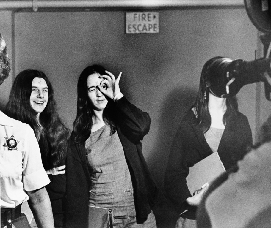 . Susan Atkins, defendant in the Tate murder trial, mimics a television film cameraman while on her way to court in Los Angeles, Calif., with fellow defendants Patricia Krenwinkel, left, and Leslie Van Houten, hidden by the camera lens, Sept. 22, 1970. (AP Photo)