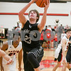 kaneland Blake Feiza (23)  goes up passed Yorkville defenders and makes a basket in the first quarter Friday as Kaneland traveled to Yorkville David Toney – For Shaw Media