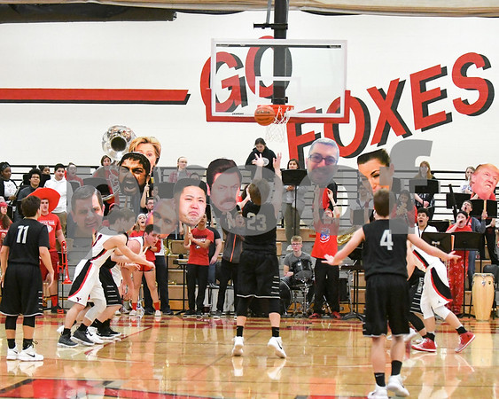 Yorkville band members hold up giant faces for a distraction to Kaneland while they take free throws throughout the second half of the game Friday night. David Toney – For Shaw Media.