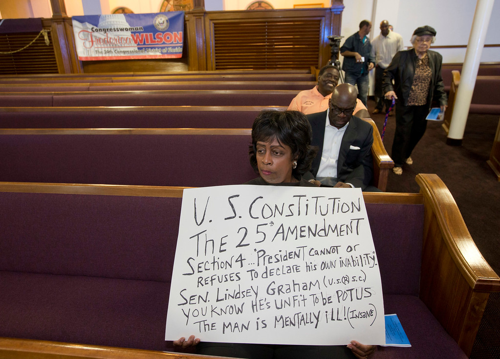 . Marva Lightbourne, with the Concerned Citizens Committee, holds a sign before a prayer vigil before watching President Donald Trump\'s State of the Union at a watch party held at the Historic Greater Bethel AME Church, Tuesday, Jan. 30, 2018, in Miami. (AP Photo/Wilfredo Lee)