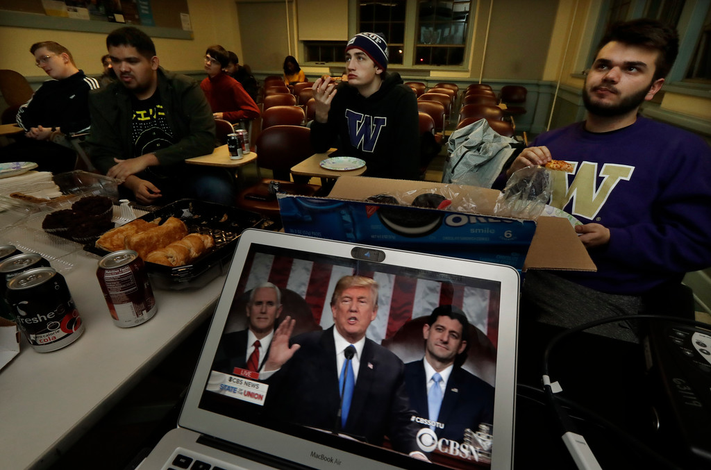 . Members of the College Republicans at the University of Washington eat pizza and other snacks as they watch a broadcast of President Donald Trump as he gives his State of the Union speech during an on-campus viewing party, Tuesday, Jan. 30, 2018, in Seattle. (AP Photo/Ted S. Warren)