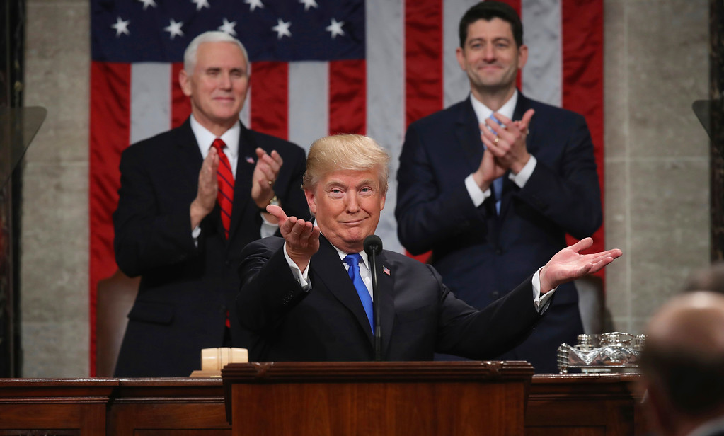 . President Donald Trump gestures as delivers his first State of the Union address in the House chamber of the U.S. Capitol to a joint session of Congress Tuesday, Jan. 30, 2018 in Washington, as Vice President Mike Pence and House Speaker Paul Ryan applaud. (Win McNamee/Pool via AP)
