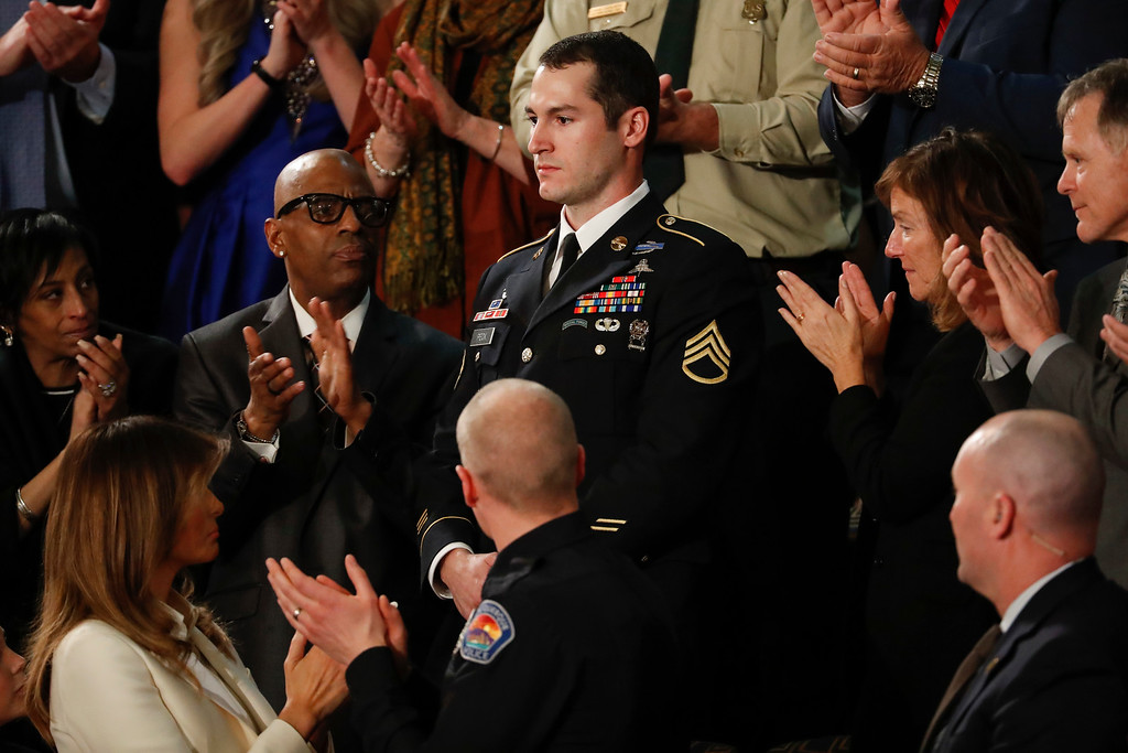 . Army Staff Sgt. Justin Peck, center,  stands as he\'s introduced by President Donald Trump during the State of the Union address to a joint session of Congress on Capitol Hill in Washington, Tuesday, Jan. 30, 2018. (AP Photo/Pablo Martinez Monsivais)