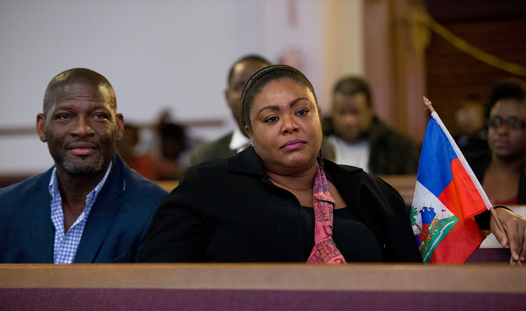 . Farah Larrieux, right, a Haitian Temporary Protected Status (TPS) recipient, holds a Haitian flag as she and her friend Louis Joseph, left, watch President Donald Trump speak during State of the Union address, as they attend a watch party at the Historic Greater Bethel AME Church, Tuesday, Jan. 30, 2018, in Miami. (AP Photo/Wilfredo Lee)