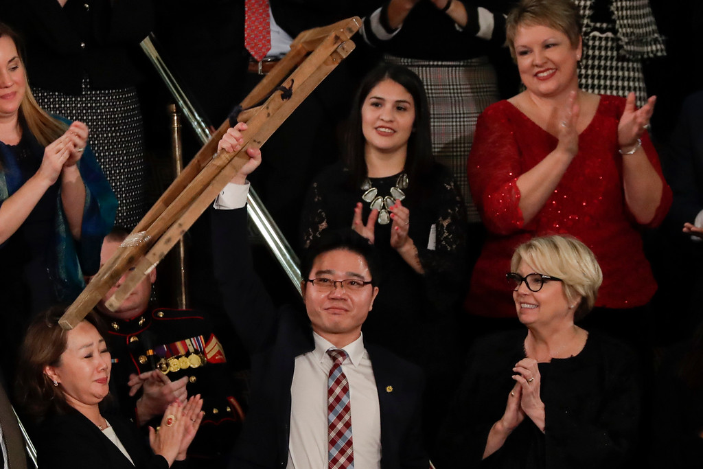. Ji Seong-ho holds up his crutches after his introduction by President Trump during the State of the Union address to a joint session of Congress on Capitol Hill in Washington, Tuesday, Jan. 30, 2018. (AP Photo/J. Scott Applewhite)
