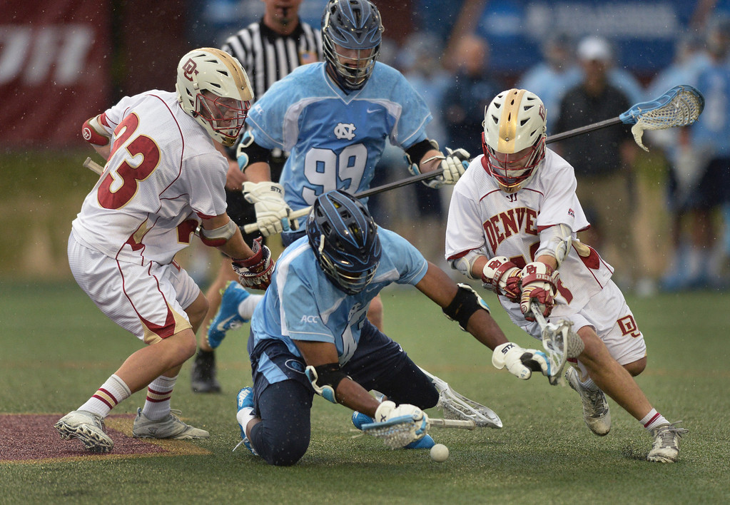 . DENVER, CO - MAY 10:  Denver midfielders Mike Riis, left and Sean Cannizzarro, right, challenged  North Carolina senior Mark McNeill, center, for the ball in the second half. The University of Denver lacrosse team defeated North Carolina 9-5 in the first round of the NCAA tournament Saturday night, May 10, 2014.  (Photo by Karl Gehring/The Denver Post)