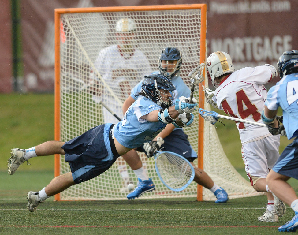 . DENVER, CO - MAY 10:  North Carolina midfielder Ryan Creighton (33) made a diving attempt to block a shot by Denver junior Sean Cannizzaro (44) in the second half. The University of Denver lacrosse team defeated North Carolina 9-5 in the first round of the NCAA tournament Saturday night, May 10, 2014.  (Photo by Karl Gehring/The Denver Post)