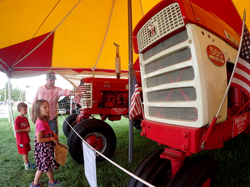 Jonathan Tressler — The News-Herald <br> Burton Township resident James Sanders points out some details on an antique International Harvester tractor on display during opening day of the 196th Great Geauga County Fair Aug. 30 as his 6-year-old daughter, Cecilia, foreground, and 5-year-old son, Michael, look on.
