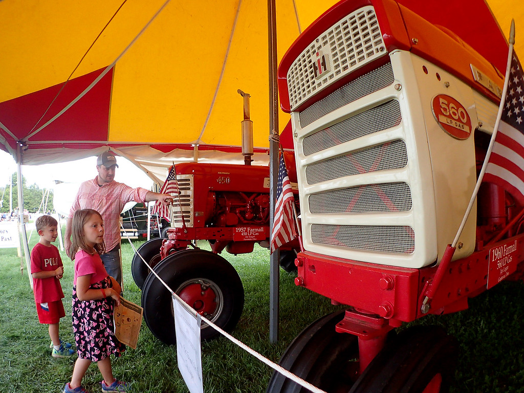 . Jonathan Tressler � The News-Herald <br> Burton Township resident James Sanders points out some details on an antique International Harvester tractor on display during opening day of the 196th Great Geauga County Fair Aug. 30 as his 6-year-old daughter, Cecilia, foreground, and 5-year-old son, Michael, look on.