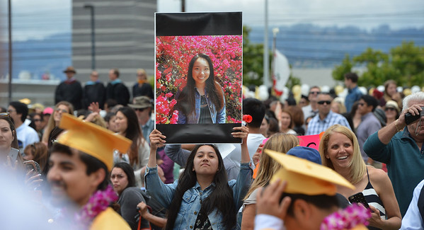 Charmaine Dimalanta holds a photo of her cousin Judith Dimalanta at Alameda High School's Class of 2016 Commencement Ceremony at Thompson Field in Alameda, Calif., on Friday, June 17, 2016. (Dan Honda/Bay Area News Group)