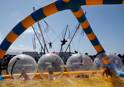 Youngsters amuse themselves in the air and on the water at the amusement park section of the Pacific Coast Dream Machines Show, Sunday morning, April 24, 2016, at the Half Moon Bay Airport in Moss Beach, Calif. (Karl Mondon/Bay Area News Group)