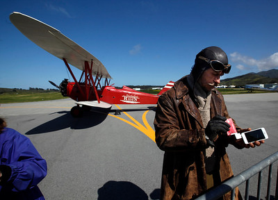 Mike Carpentiero of Nostalgic Rides swipes a customer's credit card payment on his smartphone before giving a ride aboard his 1930's-era biplane at the Pacific Coast Dream Machines Show, Sunday morning, April 24, 2016, at the Half Moon Bay Airport in Moss Beach, Calif. (Karl Mondon/Bay Area News Group)