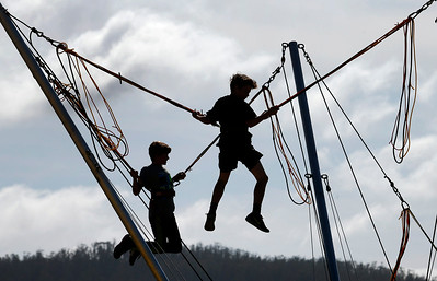 Youngsters bounce in the air at the amusement park section of the Pacific Coast Dream Machines Show, Sunday morning, April 24, 2016, at the Half Moon Bay Airport in Moss Beach, Calif. (Karl Mondon/Bay Area News Group)