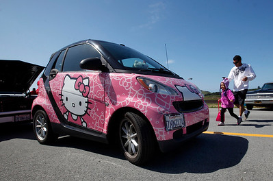 A Hello Kitty-decorated car draws the attention of color-coordinated Chloe Flores, 4, of San Carlos, who with her father Damon Flores visited the Pacific Coast Dream Machines Show, Sunday morning, April 24, 2016, at the Half Moon Bay Airport in Moss Beach, Calif. (Karl Mondon/Bay Area News Group)