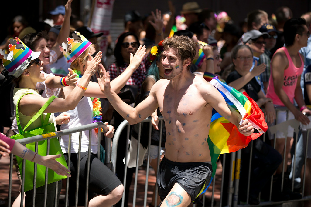 . An unidentified man carrying a rainbow flag gets high fives from spectators along the route at the 44th annual LGBT Pride parade, Sunday, June 29, 2014 on Market Street in San Francisco. (D. Ross Cameron/Bay Area News Group)