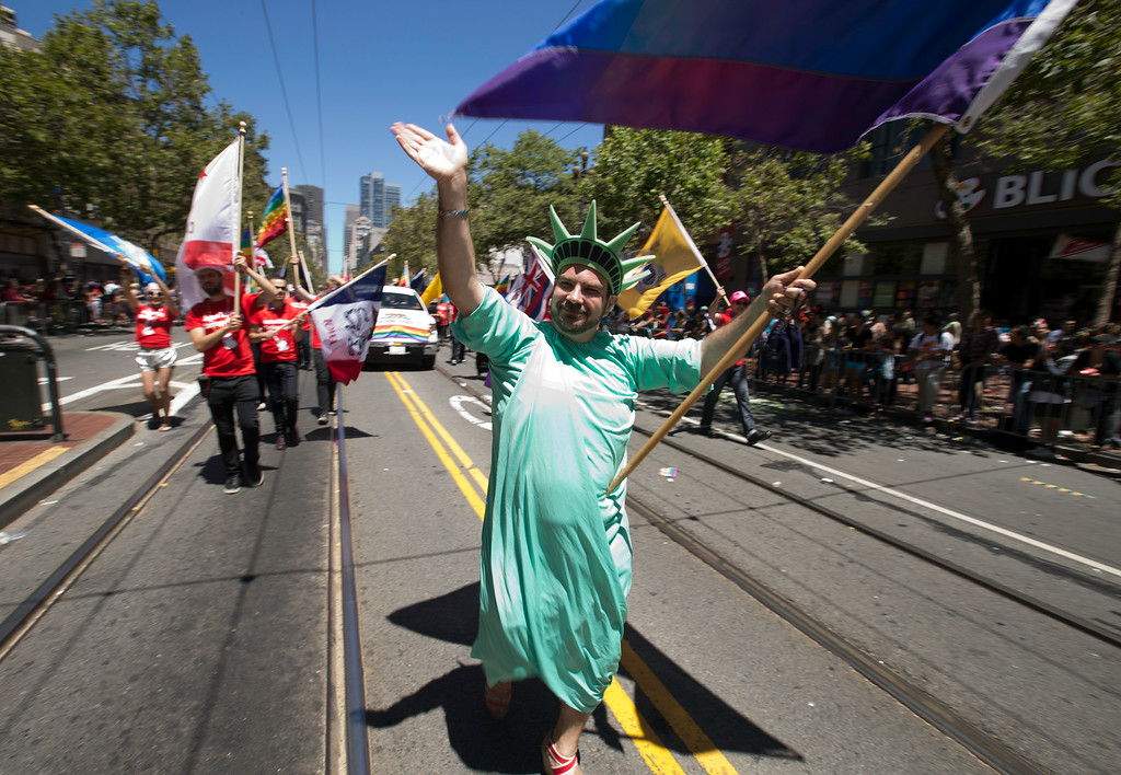 . An unidentified man costumed as the Statue of Liberty carries a rainbow flag at the 44th annual LGBT Pride parade, Sunday, June 29, 2014 on Market Street in San Francisco. (D. Ross Cameron/Bay Area News Group)