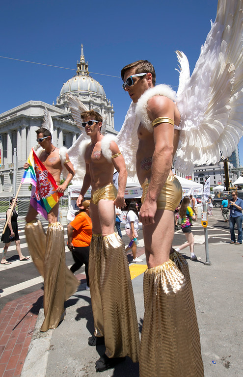 """. A trio of buff \""""angels\"""" on stilts pose for photographs at Civic Center Plaza before the start of the 44th annual San Francisco Pride Parade, Sunday, June 29, 2014 in San Francisco. (D. Ross Cameron/Bay Area News Group)"""