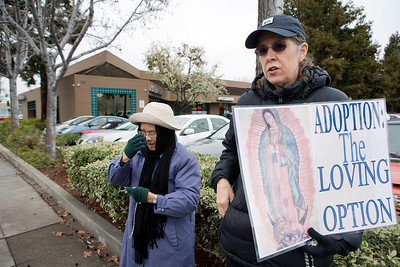 Form right, Phoebe Wise of Cupertino and Luong Dinh of Santa Clara protest and pray against abortion in front of the Planned Parenthood Health Center (in background) in Mountain View, Calif., on Thursday., Feb.6, 2014.   (LiPo Ching/Bay Area News Group)