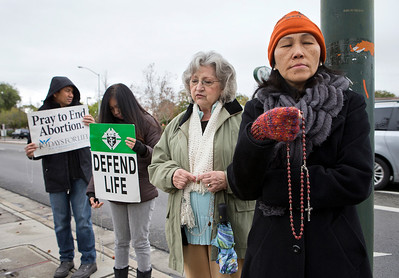 Hang Nguyen of Santa Clara, Kathy Doerr of Mountain View, Ramil Batiancila and Bernadette Batiancila, both of Fremont,  pray in protest against abortion in front of the Planned Parenthood Health Center in Mountain View, Calif., on Thursday., Feb.6, 2014.   (LiPo Ching/Bay Area News Group)