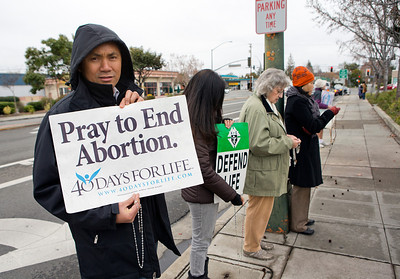 From left, Ramil Batiancila and Bernadette Batiancila, both of Fremont, protest against abortion as Kathy Doerr of Mountain View and Hang Nguyen of Santa Clara pray in protest on the sidewalk in front of the Planned Parenthood Health Center in Mountain View, Calif., on Thursday., Feb.6, 2014.   (LiPo Ching/Bay Area News Group)