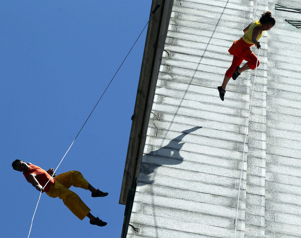. Dancers, from left, Melecio Estrella and  Amelia Rudolph founder and artistic director  with the BANDALOOP company perform an aerial dance on UC Berkeley�s Jane K. Sather Campanile in Berkeley, Calif., Saturday, April 18, 2015. (Anda Chu/Bay Area News Group)