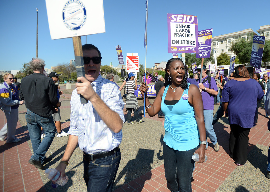 . Union members walk the picket line during a noontime rally outside of the Lake Merritt BART station in Oakland, Calif., on Friday, Oct. 18, 2013. BART workers went on strike at midnight after contract talks broke down, forcing commuters to find alternative ways to get to around the Bay Area. (Dan Honda/Bay Area News Group)