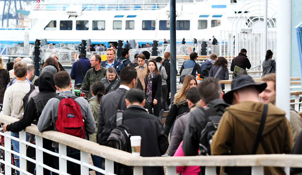 . Commuters line up to board the ferry in the early morning hour on Monday, Oct. 21, 2013 on the fourth day that BART workers are on strike in Oakland, Calif. The San Francisco Bay Ferry were running extra boats to the San Francisco Ferry building  from Oakland.  (Laura A. Oda/Bay Area News Group)