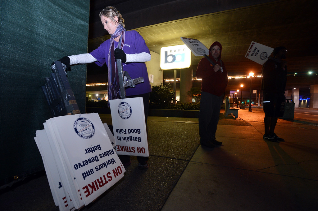 . BART employees, from left, Shari Stern, Mike Patchen and Andrew Powell picket the MacArthur station as workers at the transit agency go on strike in Oakland, Calif., on Friday, Oct. 18, 2013. (Kristopher Skinner/Bay Area News Group)