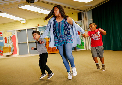 Julian Rivas Ibanez, volunteer teacher Karla Alvarez and Eduardo Fernandez Bamaca, left to right, do the chicken dance during the Physical Education portion of a kickoff to kindergarten class at Sunnybrea Elementary School in San Mateo, Calif., on Thursday, July 7, 2016. The summer class helps students who are second-language learners, and those that have never been to preschool a chance to become better prepared before they enter kindergarten. (Gary Reyes/Bay Area News Group)