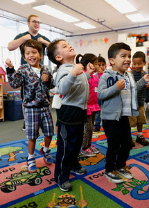 Kyrese Brown, Anitoni Henley, and Julian Rivas Ibanez, left to right, dance to the Bear Hunt song during a kickoff to kindergarten class at Sunnybrea Elementary School in San Mateo, Calif., on Thursday, July 7, 2016. At rear is volunteer teacher, Alex Mefford. The summer class helps students who are second-language learners, and those that have never been to preschool a chance to become better prepared before they enter kindergarten. (Gary Reyes/Bay Area News Group)
