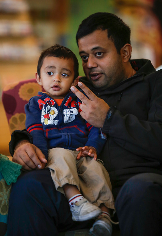 . Harsh Shah and son Ahan, 1, listen to stories about cats during chidlren\'s story time at the library in Foster City, Calif., on Saturday, Feb. 1, 2014. Story time was followed by the Homeless Cat Network\'s cat adoption fair for kids and parents interested in adopting a cat or kitten.  (John Green/Bay Area News Group)