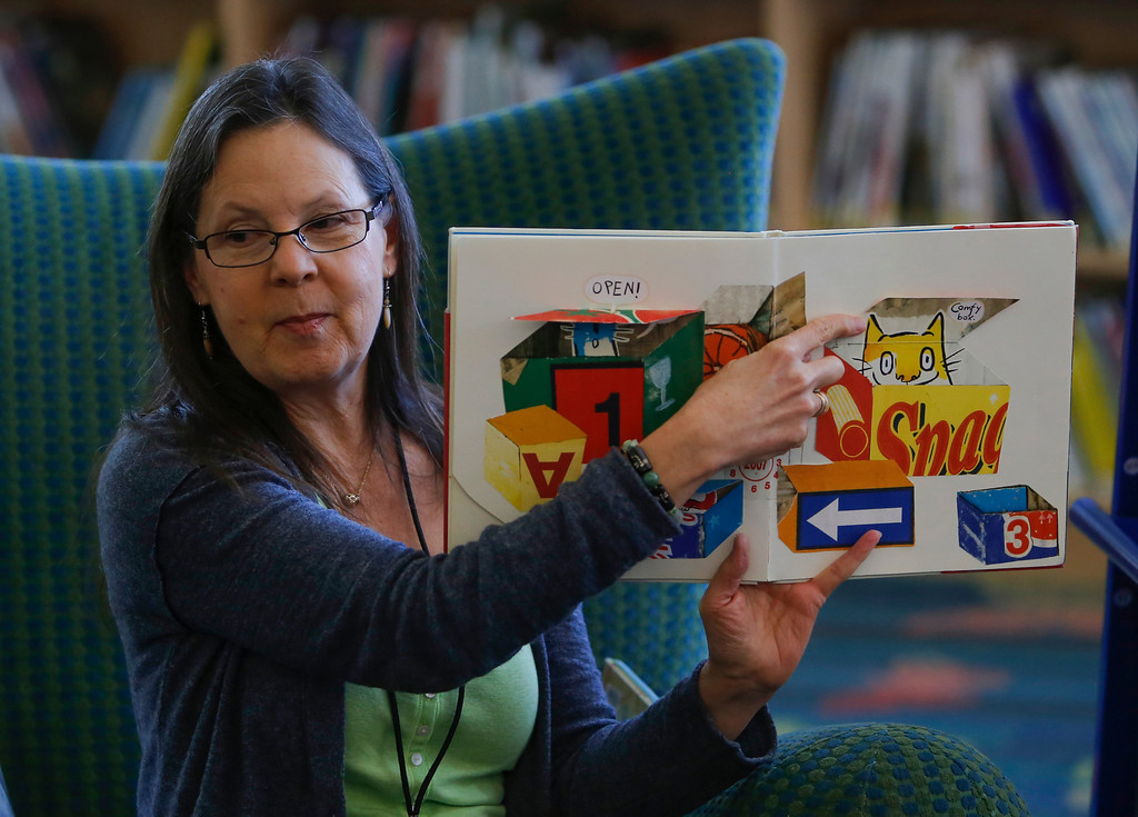 . Library Assistant Linda Napior reads a story about cats during children\'s story time at the library in Foster City, Calif., on Saturday, Feb. 1, 2014. (John Green/Bay Area News Group)