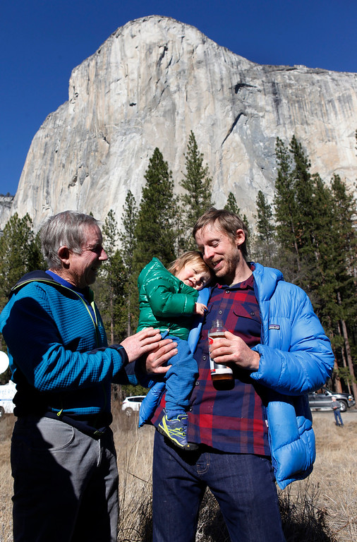 """. Climber Tommy Caldwell, 36, of Estes Park, Colo.,, holds his son, Fitz, 21 months, as his father, Mike Caldwell looks on after Tommy Caldwell and Kevin Jorgeson, 30, of Santa Rosa spoke to the media in Yosemite National Park, Calif., Thursday, Jan. 15, 2015. On Wednesday, the pair completed the ascent of the Dawn Wall of El Capitan. They were the first to do so as \""""free climbers,\"""" that is they performed their ascent without the assistance of ropes or other mechanical assistance other than being tethered to protect themselves from falls. The two men began their ascent of the half-mile of sheer granite on Dec. 27, 2014. (Patrick Tehan/Bay Area News Group)"""
