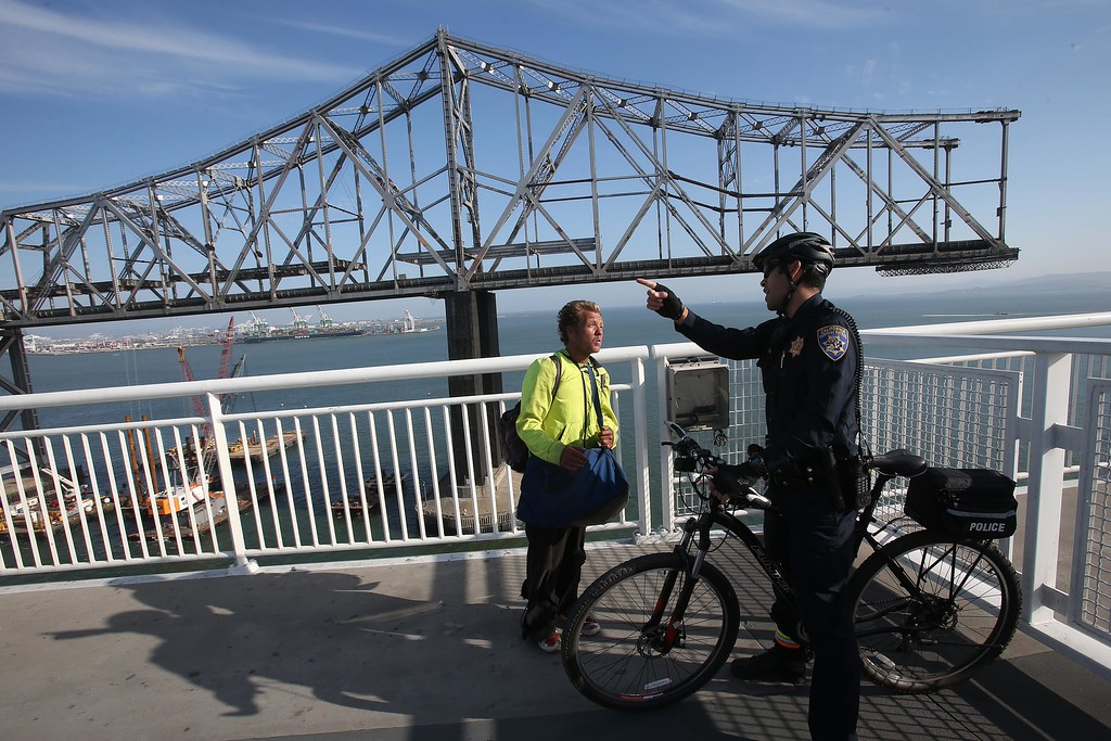 . California Highway Patrol officer Michael Aquino, right, talks with a man who wanted to cross the closed portion of the bike and pedestrian path on the Bay Bridge near Yerba Buena Island in San Francisco, Calif., on Thursday, Sept. 4, 2014. The portion of the trail closest to YBI is only open on weekends because of ongoing demolition of the old span. (Jane Tyska/Bay Area News Group)