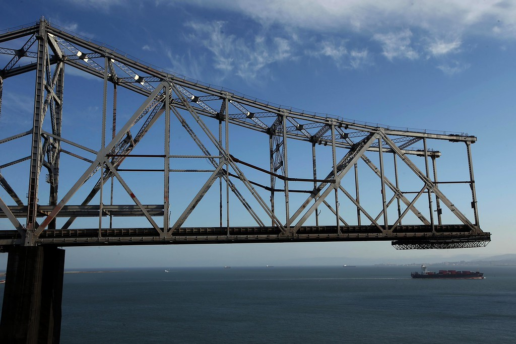 . A container ship passes by the old eastern span of the Bay Bridge in this view from the bike and pedestrian path on the new Bay Bridge near Yerba Buena Island in San Francisco, Calif., on Thursday, Sept. 4, 2014. (Jane Tyska/Bay Area News Group)