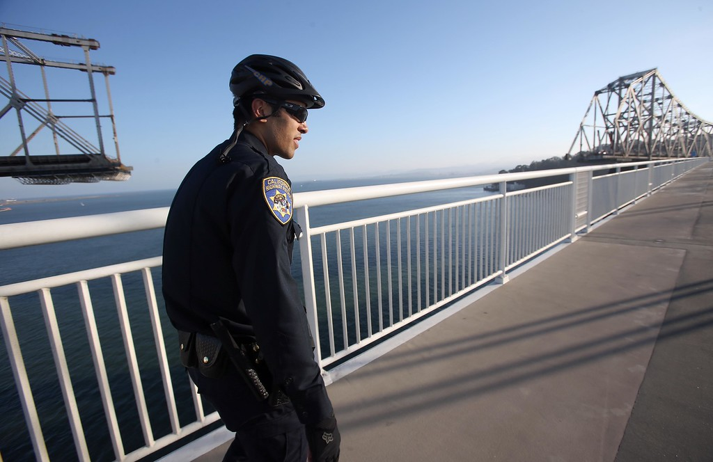 . California Highway Patrol officer Michael Aquino walks along the bike and pedestrian path on the new Bay Bridge near Yerba Buena Island in San Francisco, Calif., on Thursday, Sept. 4, 2014. The portion of the trail closest to YBI is only open on weekends because of ongoing demolition of the old span. (Jane Tyska/Bay Area News Group)