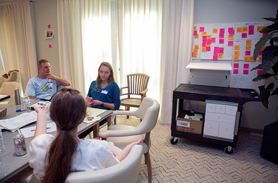 From background left, volunteer mentor Ted Barber and volunteer Lucy Volino, 14, speak to Alisah Bowman-McVay, 15, foreground,  about their design for an adjustable cart for a bedside dialysis machine (prototype at right) during the Design Daze event sponsored by The DFarm at the Ronald McDonald House at Stanford in Palo Alto, Calif., on Saturday, August 13, 2016. (LiPo Ching/Bay Area News Group)