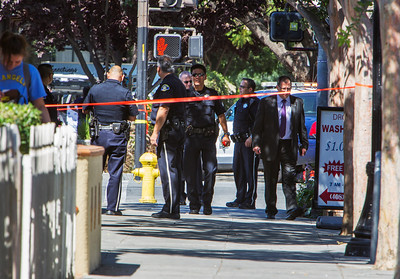 San Jose Police Department investigators search the intersection of E. San Carlos St. and S. 11th Street after a shooting homicide in downtown San Jose, Calif., on Tuesday, June 28, 2016. (LiPo Ching/Bay Area News Group)