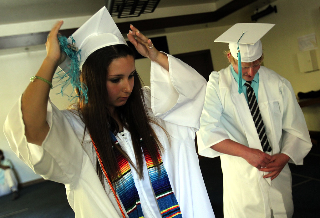 . Class of 2013 graduates Esperanza Dillard, 18, of Livermore and Joshua Mora, 18, of Fremont, from left, put on their cap and gowns as they prepare for their graduation ceremony at the California School for the Deaf in Fremont, Calif., on Friday, June 7, 2013. Forty seniors make up the school\'s 141st CSD graduating class. (Anda Chu/Bay Area News Group)