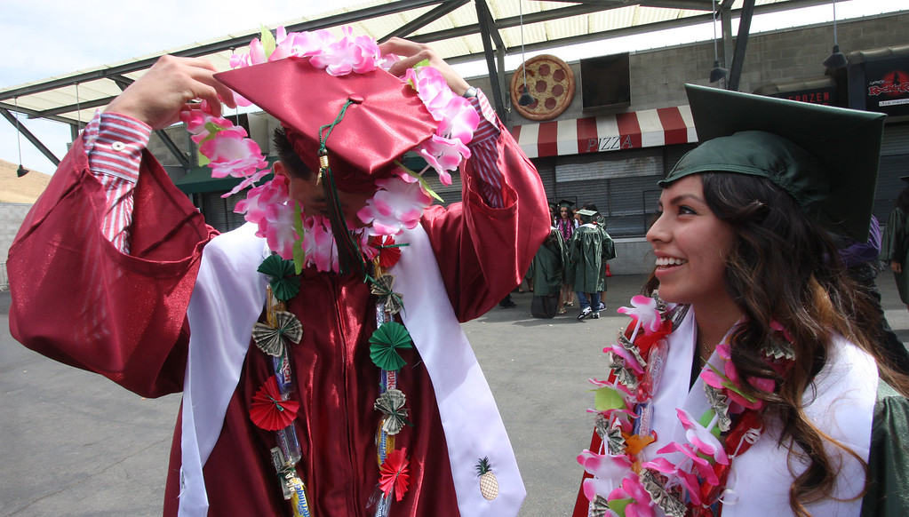 . Alexis Ceballos, left, struggles to get a flower lei over his mortarboard as Stephanie Barcenas watches while waiting for the start of graduation ceremonies for Mt. Diablo High School held at the Sleep Train Pavilion in Concord, Calif., on Sunday, June 9, 2013. It is the 100th anniversary of the school,  which graduated three students in 1913 and 300 on Sunday. (Jim Stevens/Bay Area News Group)